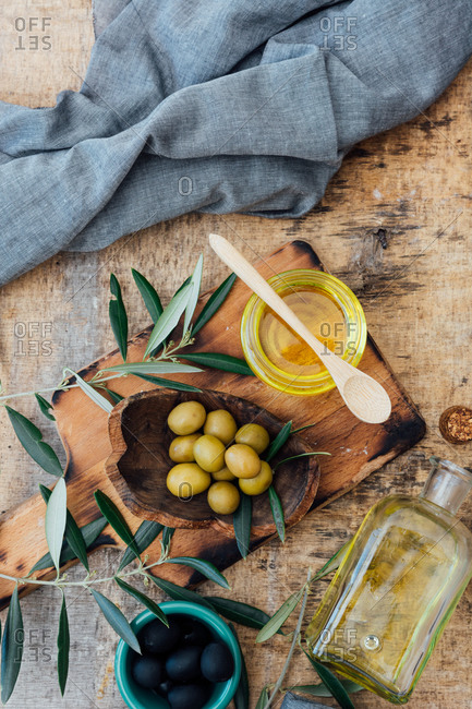 Top view olive oil in a glass jar ready to prepare delicious salad with ripe red tomatoes at wooden rustic table