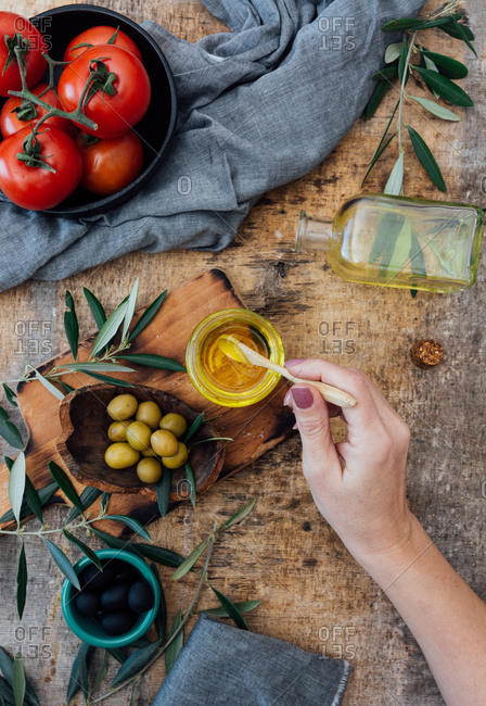 Top view of crop female taking olive oil from glass jar while cooking delicious salad with ripe red tomatoes at wooden table