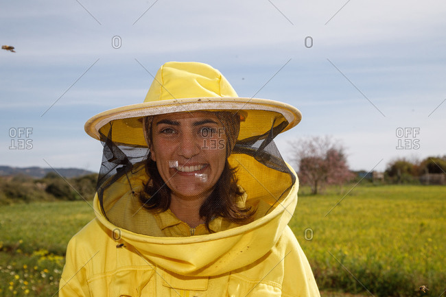 Positive female beekeeper in yellow protective costume and mask smiling and looking at camera while standing in green field in apiary in sunny summer day