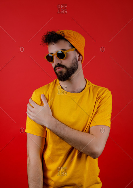 Serious bearded guy in stylish yellow outfit touching shoulder and looking away on red background