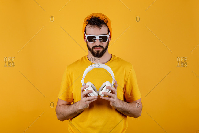 Bearded guy in stylish outfit carrying white contemporary headphones before listening to music against yellow background