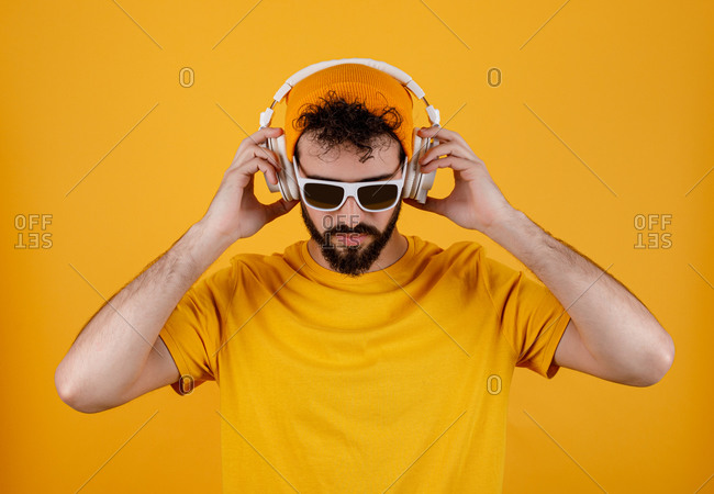 Bearded guy in stylish outfit listening to music on a white contemporary headphones against yellow background
