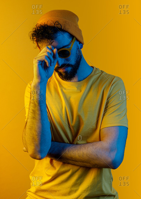 Serious thoughtful bearded male in stylish sunglasses and hat touching face while standing under bright yellow light