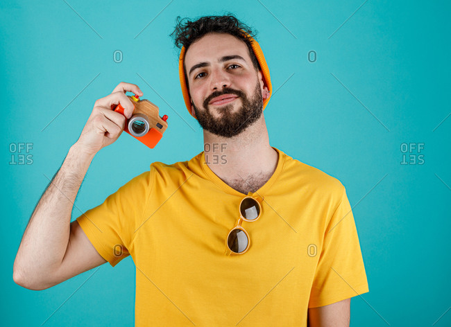 Happy bearded guy in trendy outfit smiling and taking pictures with small photo camera against turquoise background looking at camera