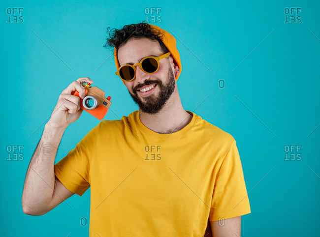 Happy bearded guy in trendy outfit smiling and taking pictures with small photo camera against turquoise background