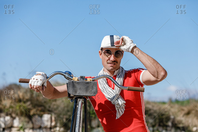 Stylish adult male with mustache in sunglasses and bright red shirt in composition with scarf and gloves touching striped cap while leaning on bike handlebar against blurred grassed hill and blue sky in nature