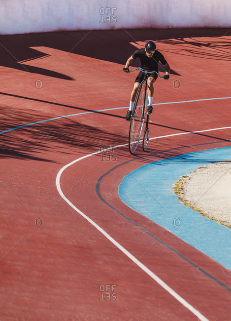 From above adult focused cyclist in black sportswear and helmet riding penny farthing along racetrack at sports stadium while getting ready for competition in sunny day