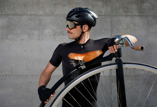Calm determined man in black activewear and helmet looking away while standing on asphalt road and leaning on high wheel bicycle against concrete wall in sunny day