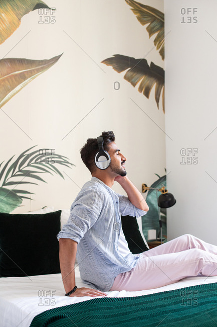 Side view of thoughtful bearded Hispanic male in headphones sitting on bed and enjoying good music at home