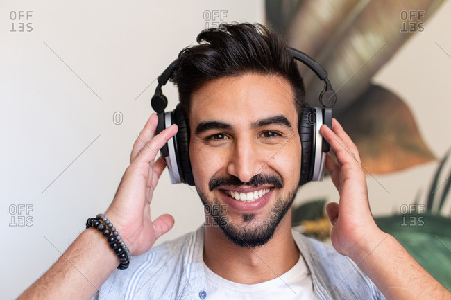 Happy ethnic guy in headphones smiling and looking at camera while listening to music at home