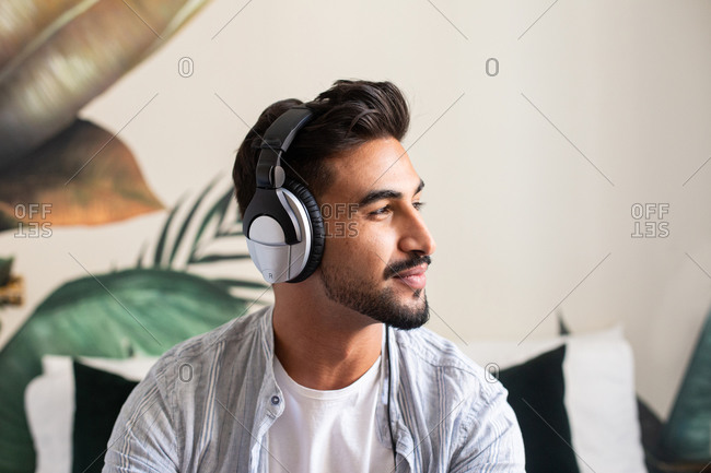 Happy ethnic guy in headphones smiling and looking away while listening to music at home