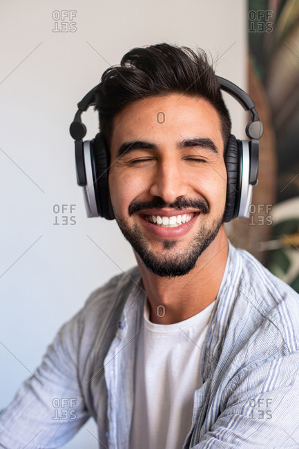 Happy ethnic guy in headphones smiling with closed eyes while listening to music at home