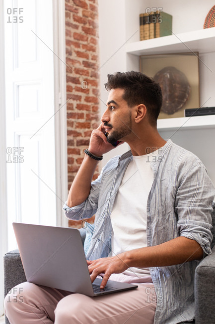 Bearded ethnic man using laptop and speaking on smartphone while working on remote project at home