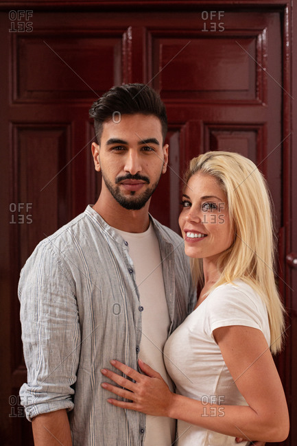 Positive diverse man and woman hugging each other and looking at camera while standing against flat door