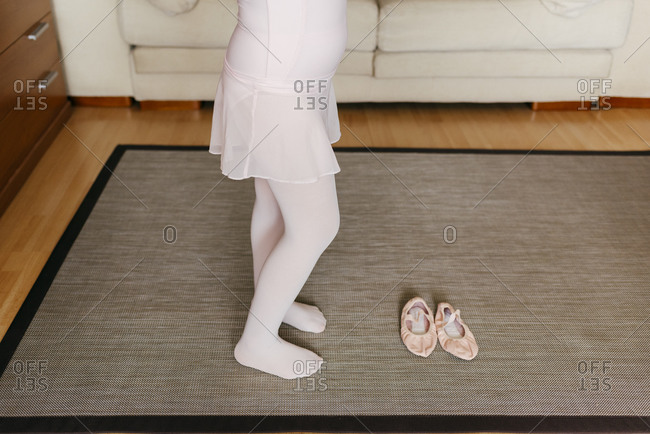 From above anonymous girl in light leotard and tights standing on carpet near dance shoes during training at home