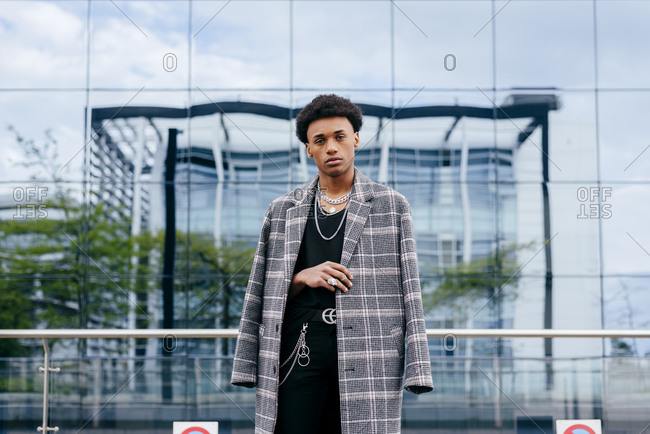Confident young African American male teenager model in trendy tartan coat and stylish accessories looking at camera while standing against contemporary building with glass wall