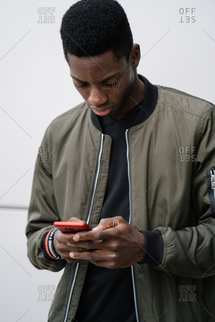 Young African American man in casual clothes standing against gray wall and texting message on smartphone on city street