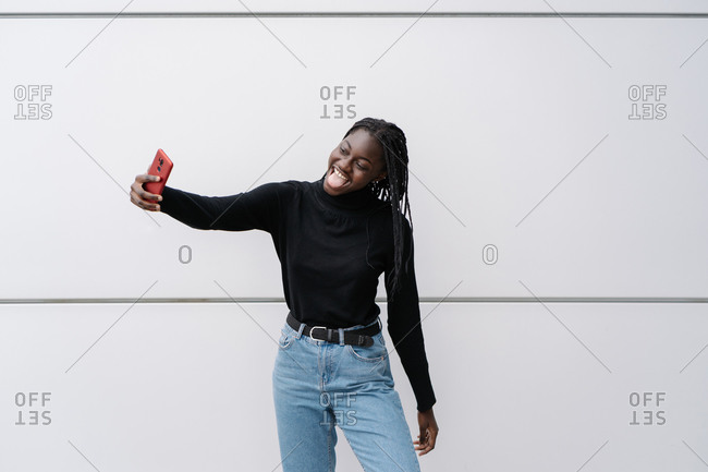 Delighted African American woman using smartphone on street