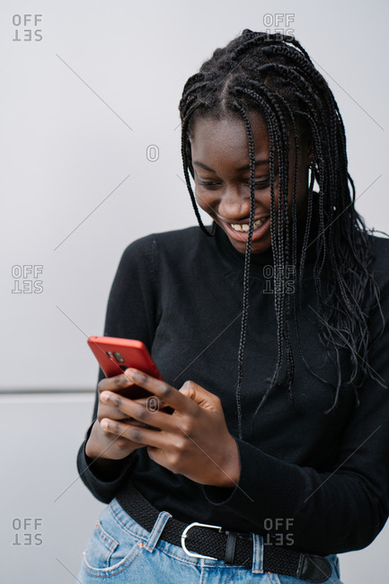 Cheerful young black lady in casual clothes smiling and texting message on smartphone while standing near gray wall of modern building on city street