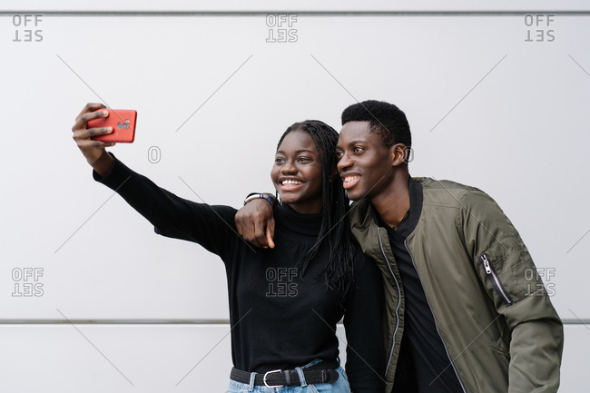 Happy African American man and woman in casual clothes hugging each other and taking selfie while standing against gray wall of modern building on city street