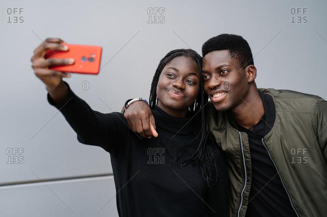 Cheerful black couple taking selfie on street