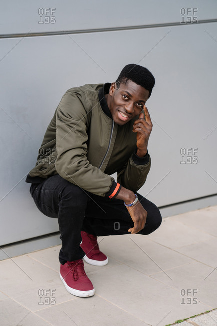 Full body positive African American man in casual clothes smiling for camera and touching face while sitting on haunches near gray wall of modern building on city street