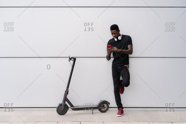 Full body black male in casual clothes leaning on gray building wall near electric scooter and browsing smartphone on contemporary city street