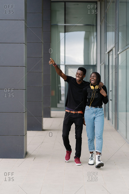 Happy black couple walking outside modern building