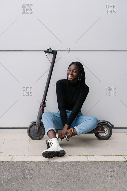 Full length delighted African American female in casual clothes smiling and looking at camera while sitting on electric scooter near gray building wall on modern city street