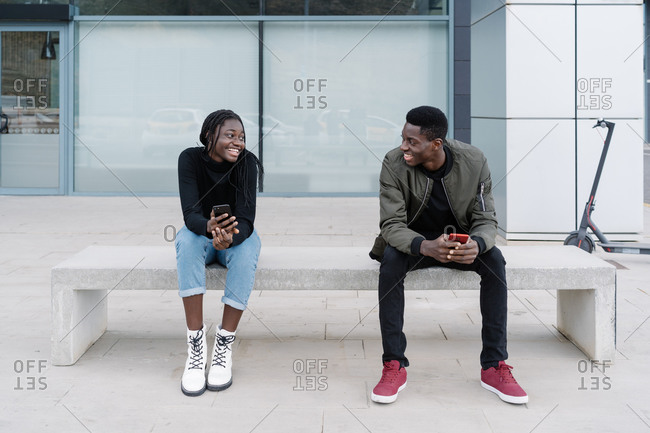 Full body young African American man and woman with smartphones smiling and looking at each other while sitting on bench and making acquaintance on modern city street