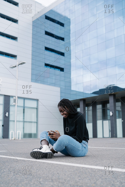 Full body delighted black female in casual clothes smiling and browsing smartphone while sitting on parking lot with crossed legs outside modern building on city street