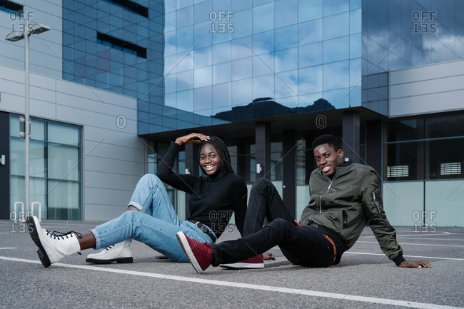 Full body young black man and woman in casual clothes smiling and looking at camera while sitting on asphalt ground on parking lot outside contemporary building on city street