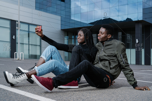 Full body black man and woman in casual clothes sitting on asphalt parking lot and taking selfie during date on modern city street