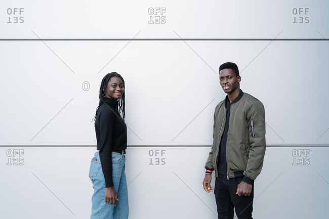Contemporary African American male and female in casual clothes looking at camera while standing near gray building wall on city street