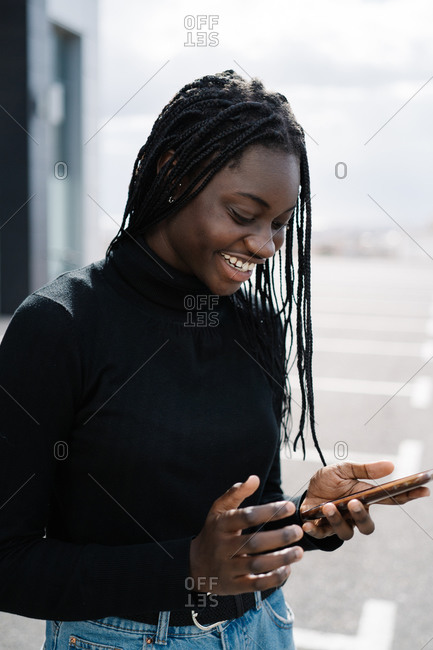 Cheerful ethnic lady using smartphone on parking lot