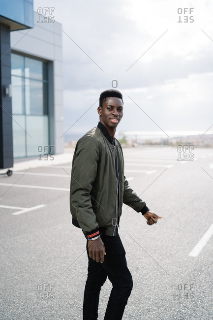 Positive African American man in casual clothes looking at camera while walking on asphalt parking lot against cloudy sky on city street