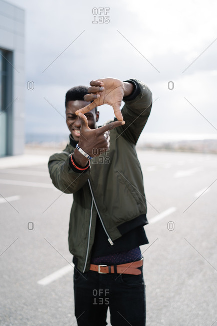African American male in casual clothes squinting and making frame with hands while standing on parking lot against cloudy sky on city street