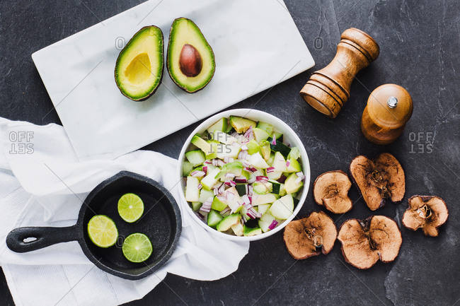 Top view of bowl with delicious avocado salad in composition with lime halves in skillet and cut avocado with fried apple chips on table
