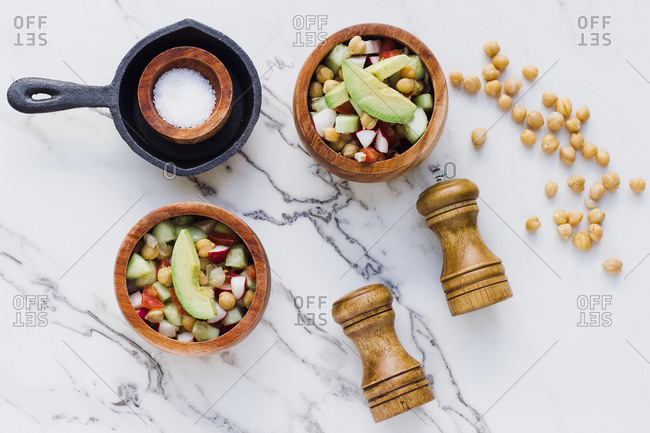 Flat lay of arranged wooden bowls with avocado salad with chickpeas composed on white marble table with salt and pepper seasonings