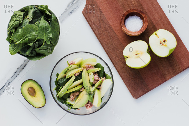 Top view of bowl with delicious salad with tuna apple and avocado composed with board with apple halves and bowl of fresh spinach on white marble surface