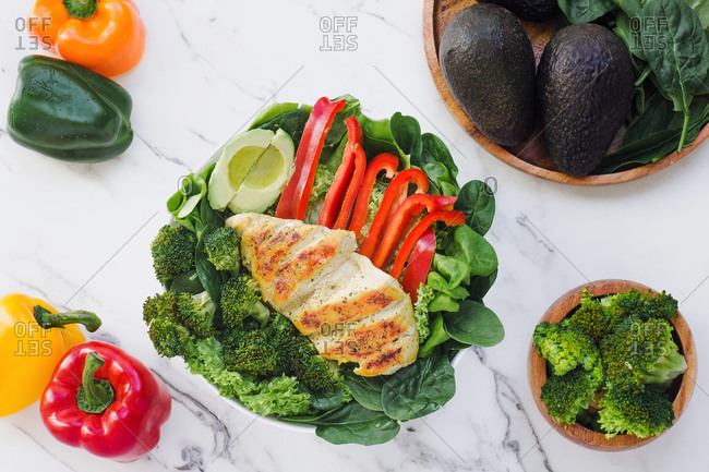From above roasted chicken with broccoli, red pepper and halved avocado ono a bed of green leaves in a marble table