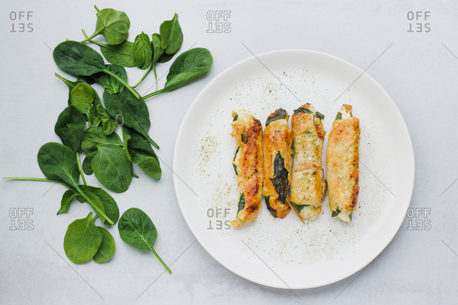Top view of yummy rolls of roasted chicken fillet placed on plate near fresh spinach leaves on light gray table