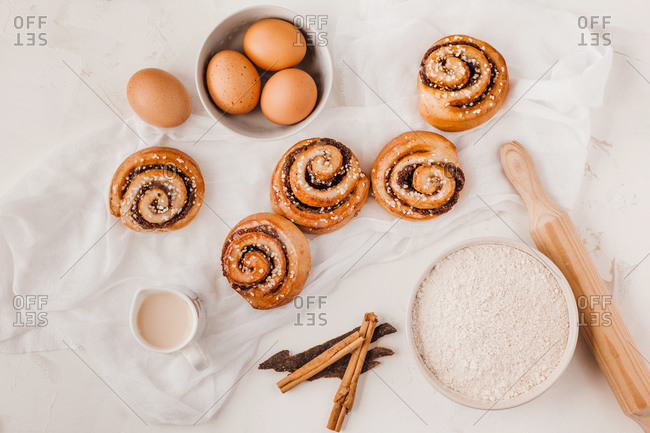 From above composition of delicious cinnamon rolls and ingredients for baker on white table with napkin