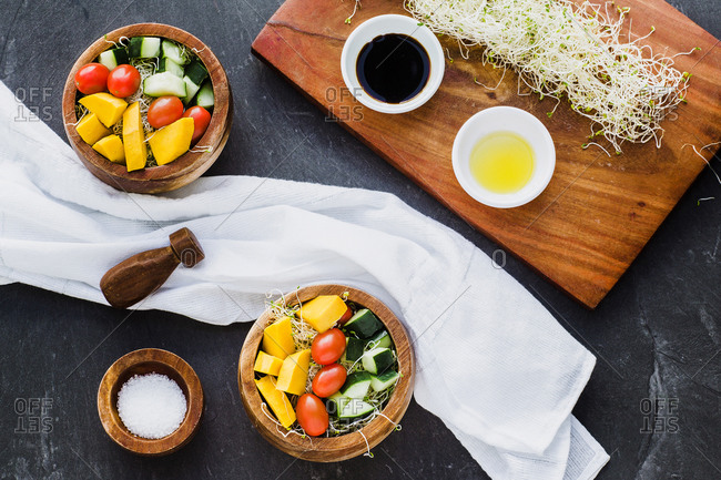 Flat lay of wooden bowls filled with microgreens and topped with raw zucchini and pumpkins with cherry tomato on slate surface
