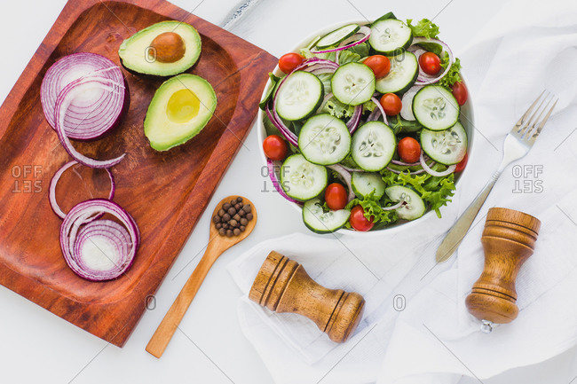 Flat lay of bowl with salad of cucumber and lettuce with red onion and cherry tomatoes on white table with board and seasonings around