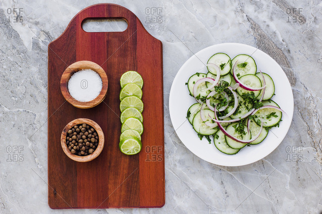 Flat lay of wooden board with salt pepper and sliced lime composed on gray marble surface with plate of salad with cucumber and chopped greens with red onion