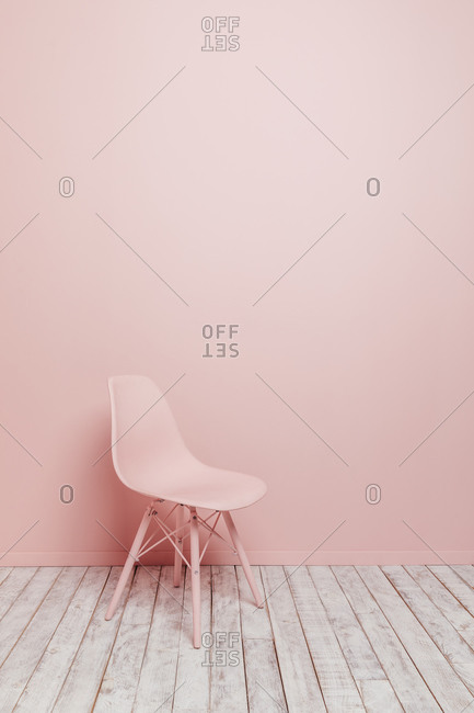 Side view of a single design pink chair on a pink background