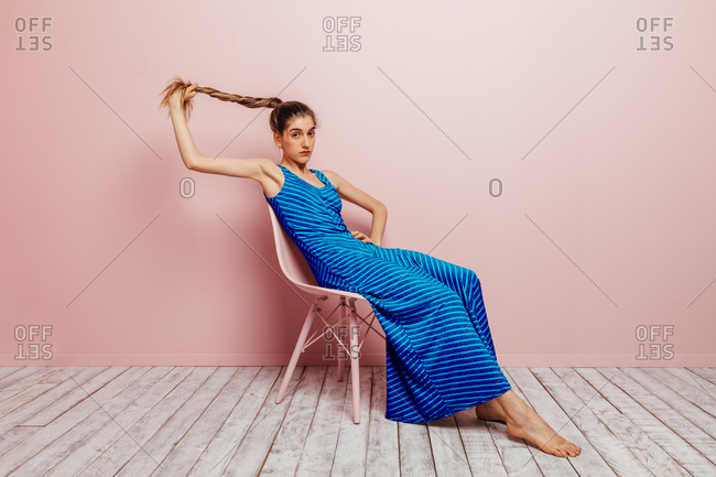 Side view of young woman in blue dress barefoot looking at camera holding ponytail while sitting with in chair and looking at camera on minimalist pink background