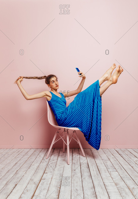 Side view of woman sitting in a chair lifting legs up barefoot looking at mobile phone while taking a selfie holding ponytail up on pink background