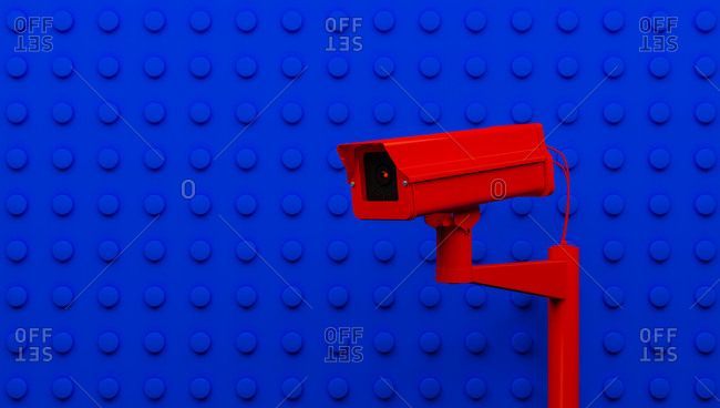 Red surveillance camera on blue background monitoring people on the street. Camera to search for quarantine offenders caused by Coronavirus